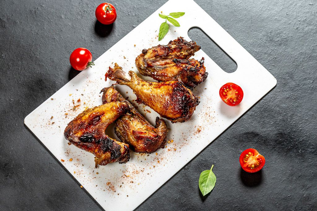Top view pieces of baked chicken with tomatoes and Basil on a black background (Flip 2019)
