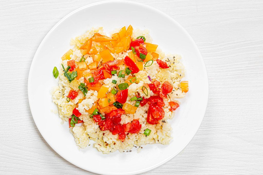 Top view porridge couscous on a white plate with vegetables