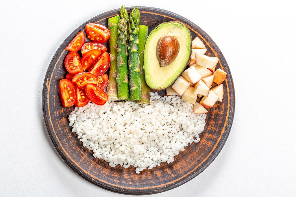 Top view, rice with avocado, tomatoes, asparagus and apples