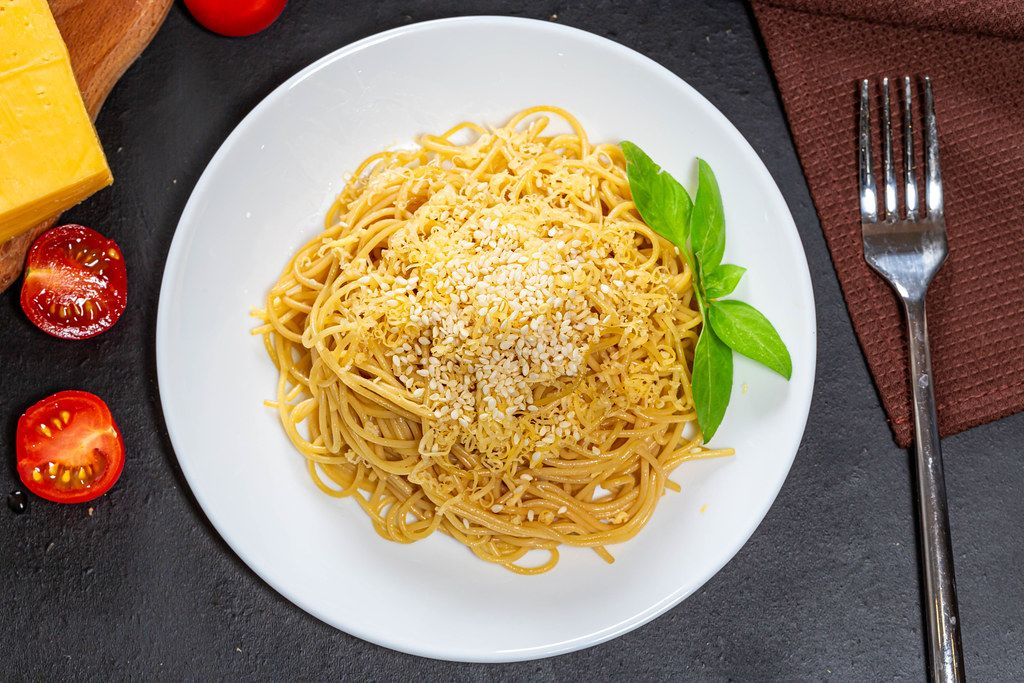 Top view spaghetti with cheese, sesame seeds and Basil leaves on a black background