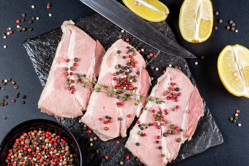 Top view, steaks with spices, lemon slices and a knife on a dark background