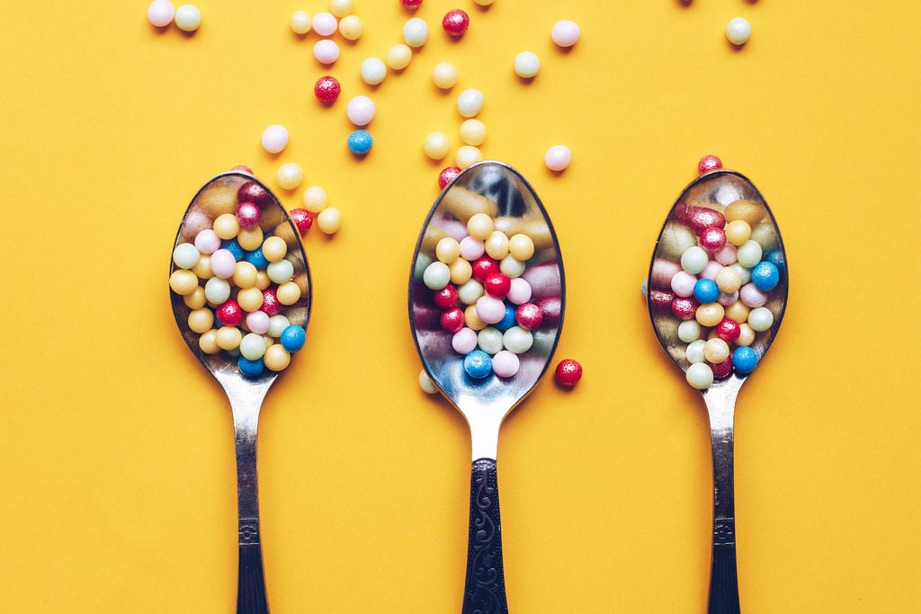 Top view three spoons with colorful sprinkles on yellow background.