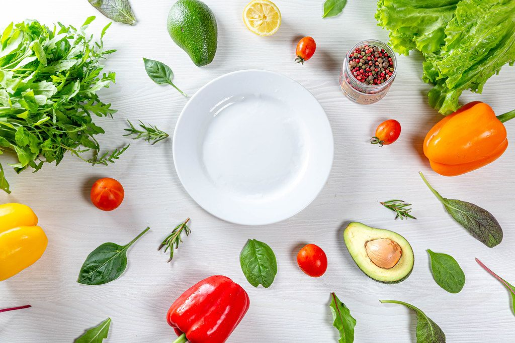 Top view vegetables, herbs and spices around a white plate. Healthy eating concept