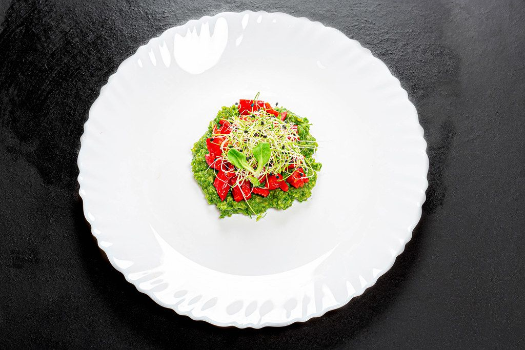 Top view vegetarian salad with fresh vegetables and onion seed sprouts on a white plate