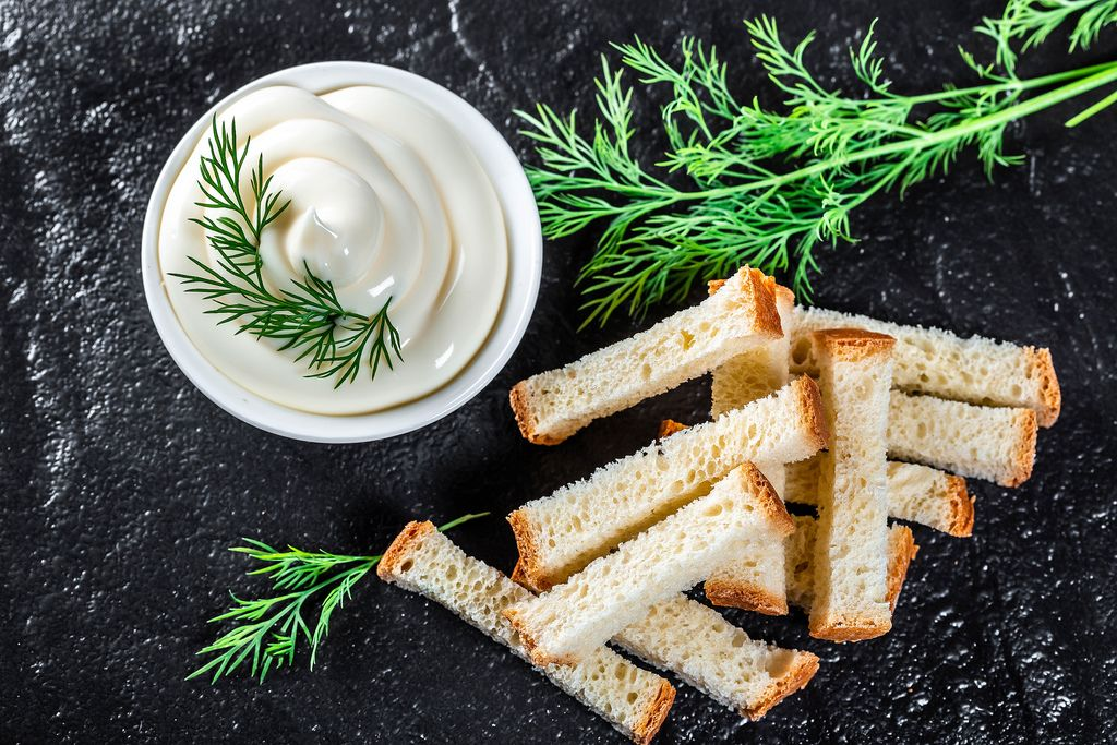 Top view white sauce and crackers with fresh dill on black stone background