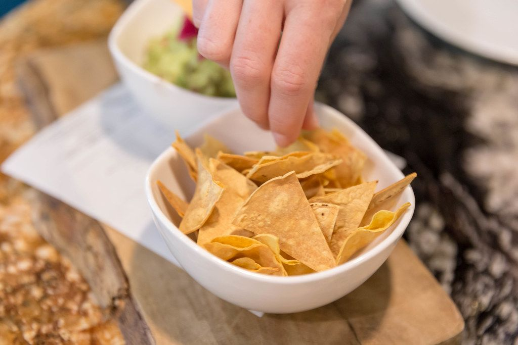 Tortilla chips to dip in guacamole (avocado cream) served on a wooden beam at Fit Kitchen Restaurant in Barcelona, Spain