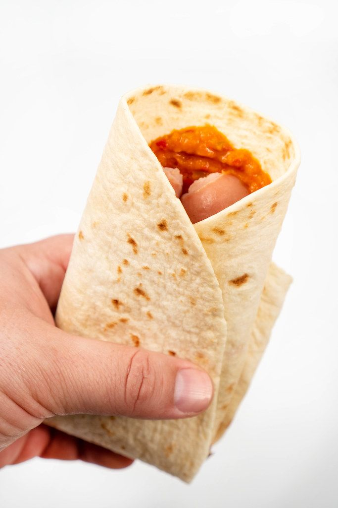 Tortilla with Sausages in the hand above white background