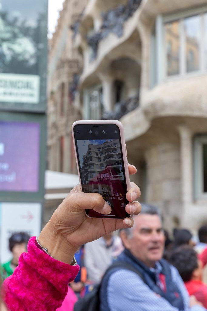 Tourist schießt ein Handyfoto von Designerhaus und Kulturstätte Casa Milà in Spaniens Hauptstadt Barcelona