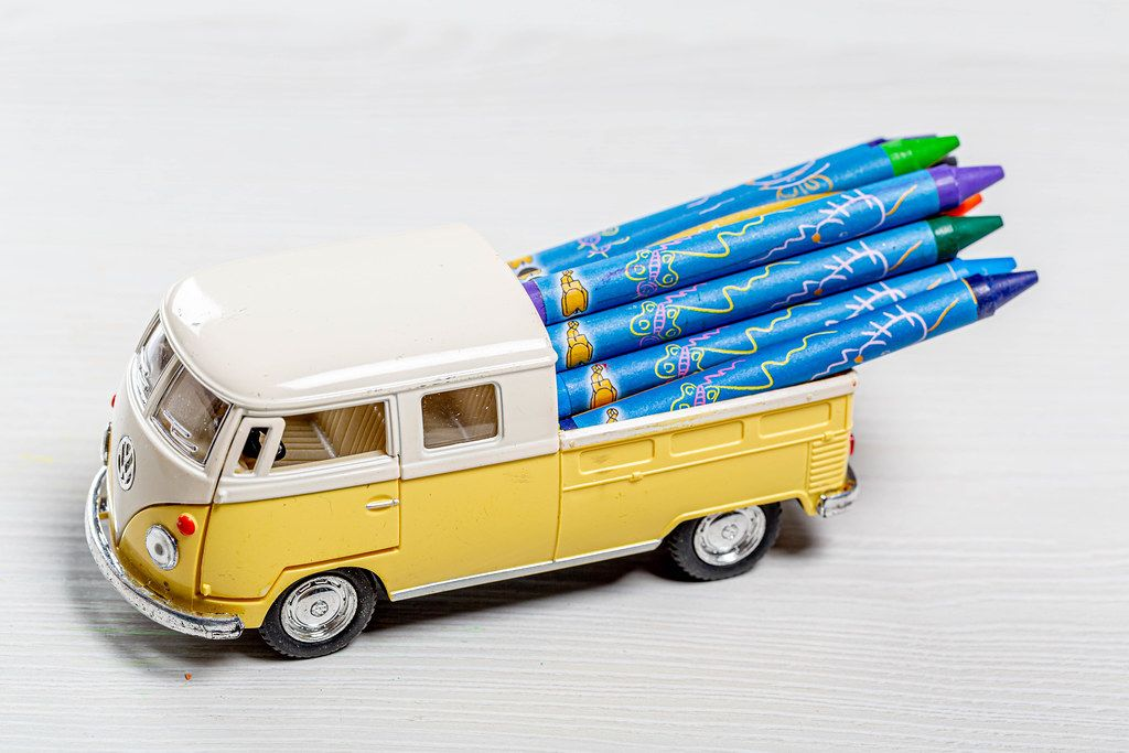 Toy car with colored pencils in the trunk. The concept of children's time in school