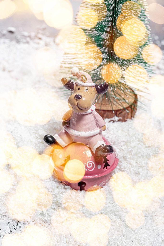 Toy deer on white snow with Christmas tree and Golden bokeh background