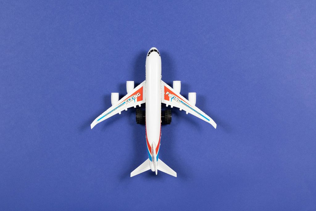 Toy plane on blue paper background