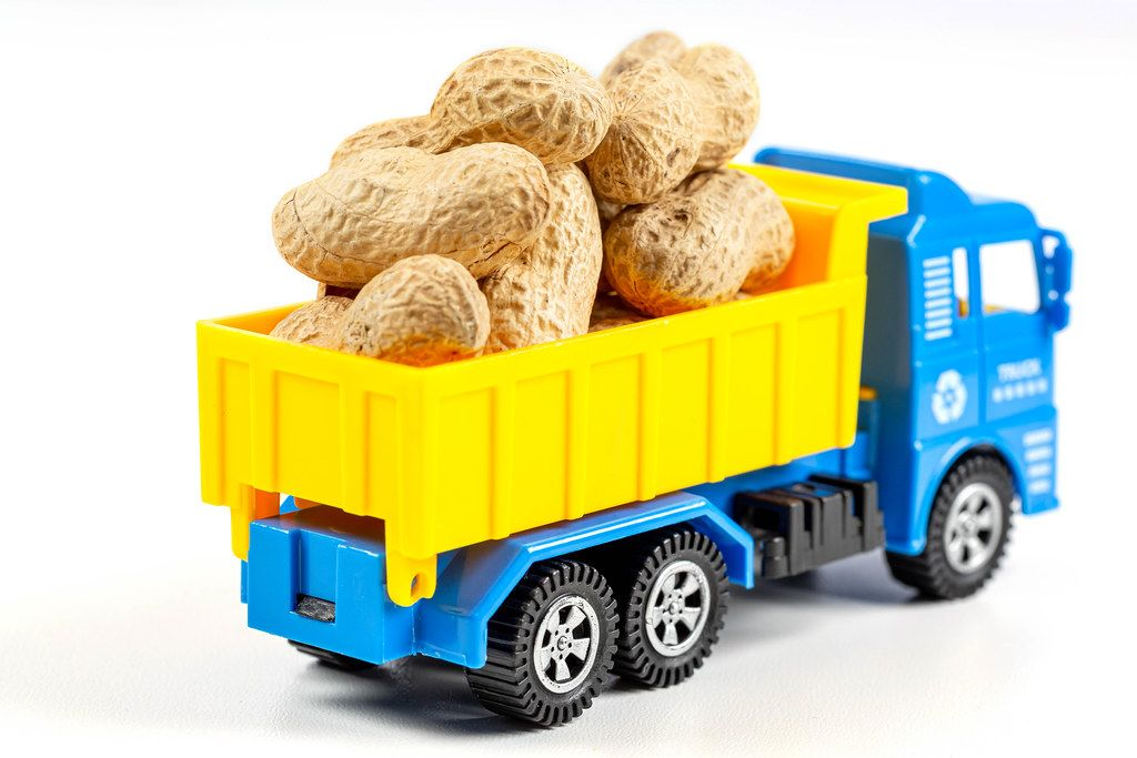Toy truck with peanuts on white background