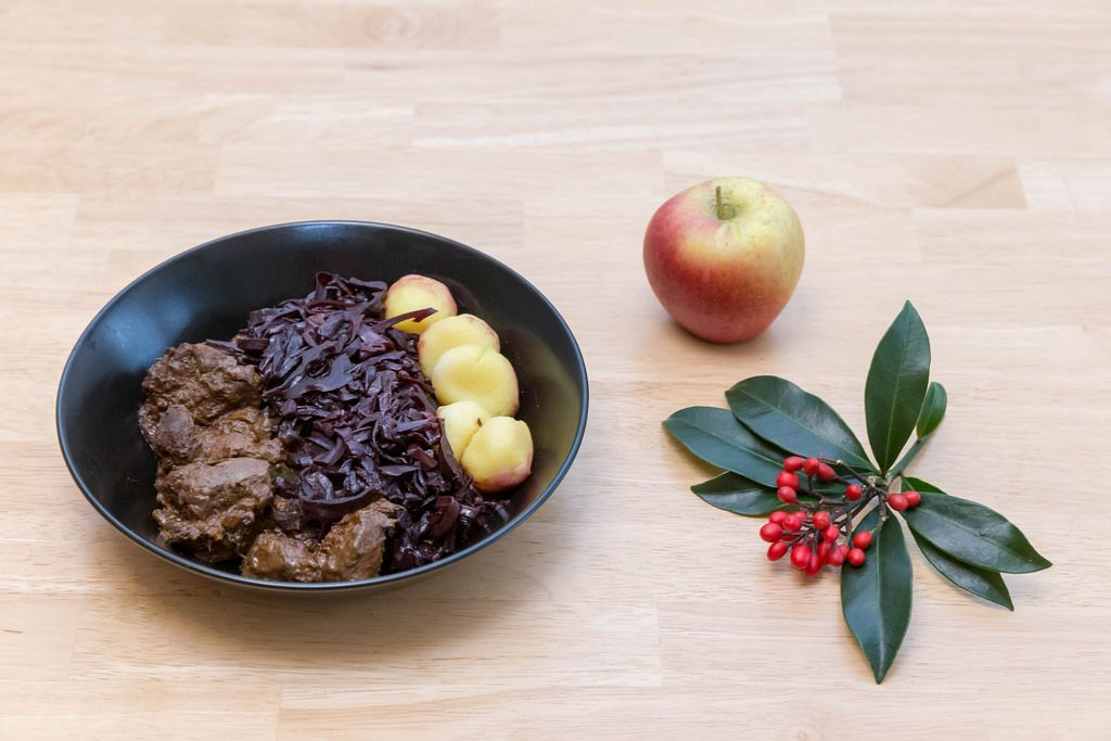 Traditional beef stew with apple beetroot salad and potato dumplings with a twig and an apple on a wooden table