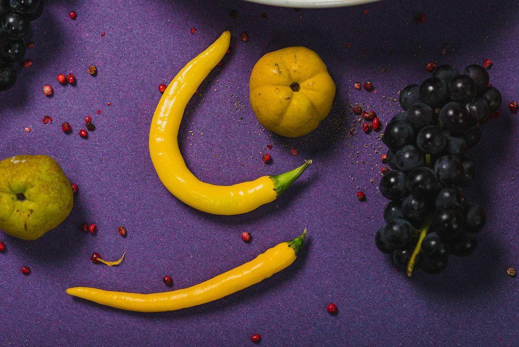 Trauben, gelbe Chilischoten und Quitte auf einem lila Tisch