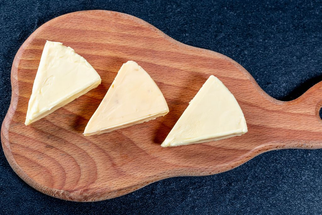 Triangles of processed cheese on the kitchen Board
