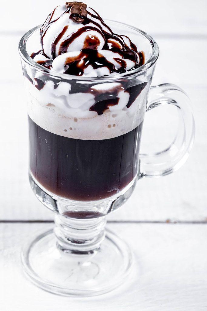 Trinkglas mit einem Sahnekaffee, Schlagsahne, Kaffeebohne und Schokoladensauce auf einem weißen Holztisch