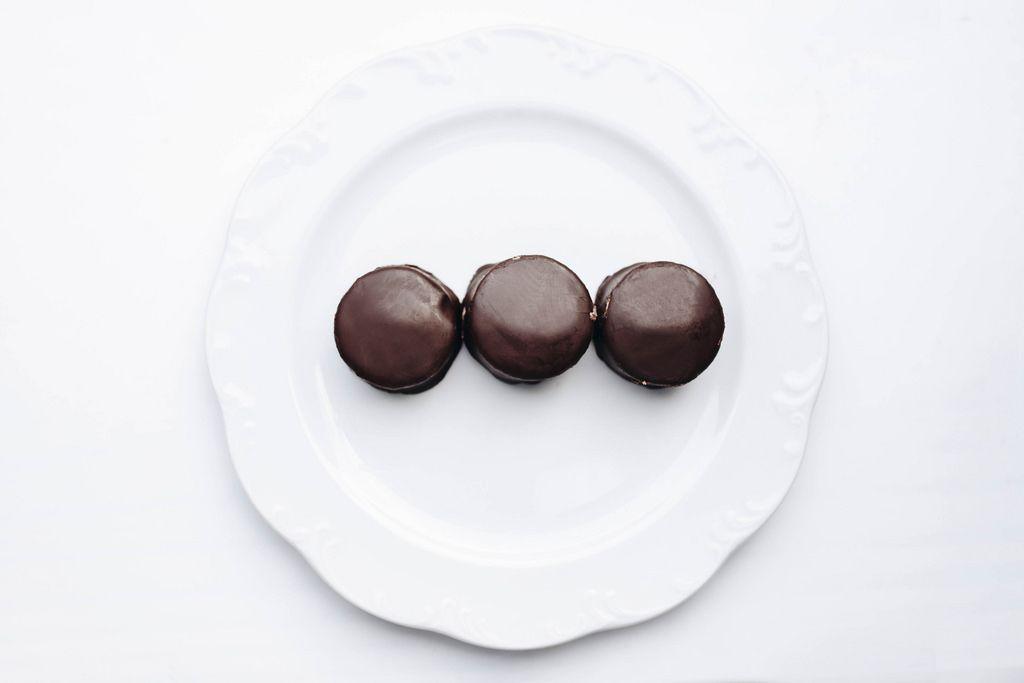Türkische Nachspeise Halva mit Schokolade vor weißem Hintergrund. Draufsicht