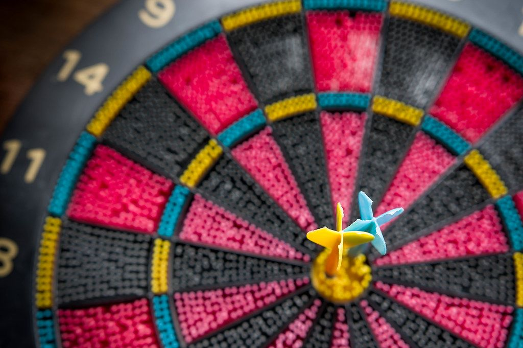 Two Darts pinned in Bullseye of a Colorful Plastic Toy Dart Board
