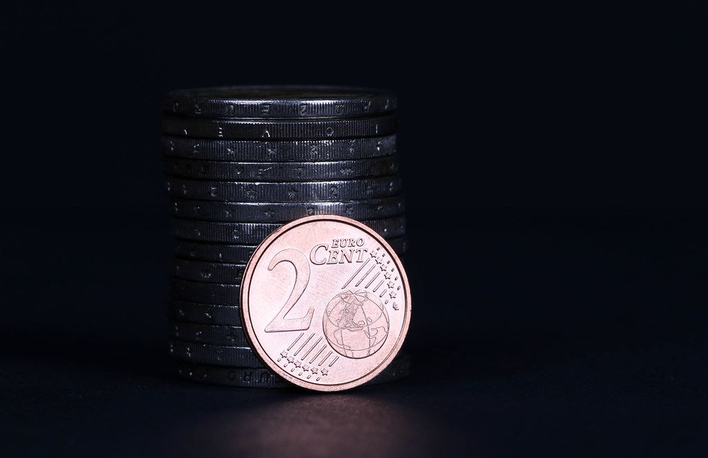 Two Euro cent coin placed in front of piles of coins