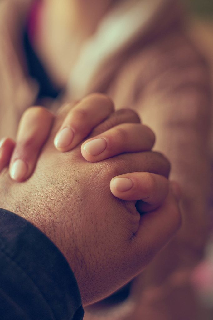 Two hands together, a man and woman holding hands. Husband and wife together. Support, loving, caring and understanding concepts