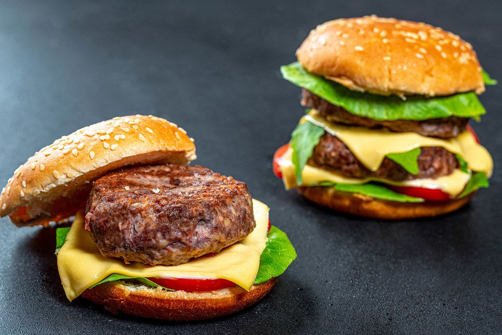 Two homemade Burger with beef patties, cheese and vegetables on black background