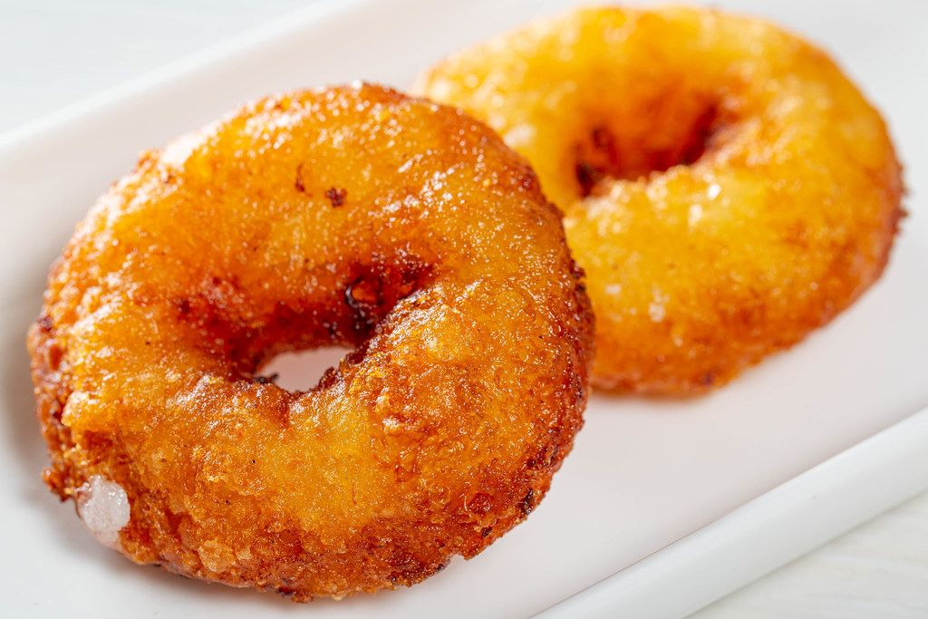 Two homemade fried donuts on a white plate