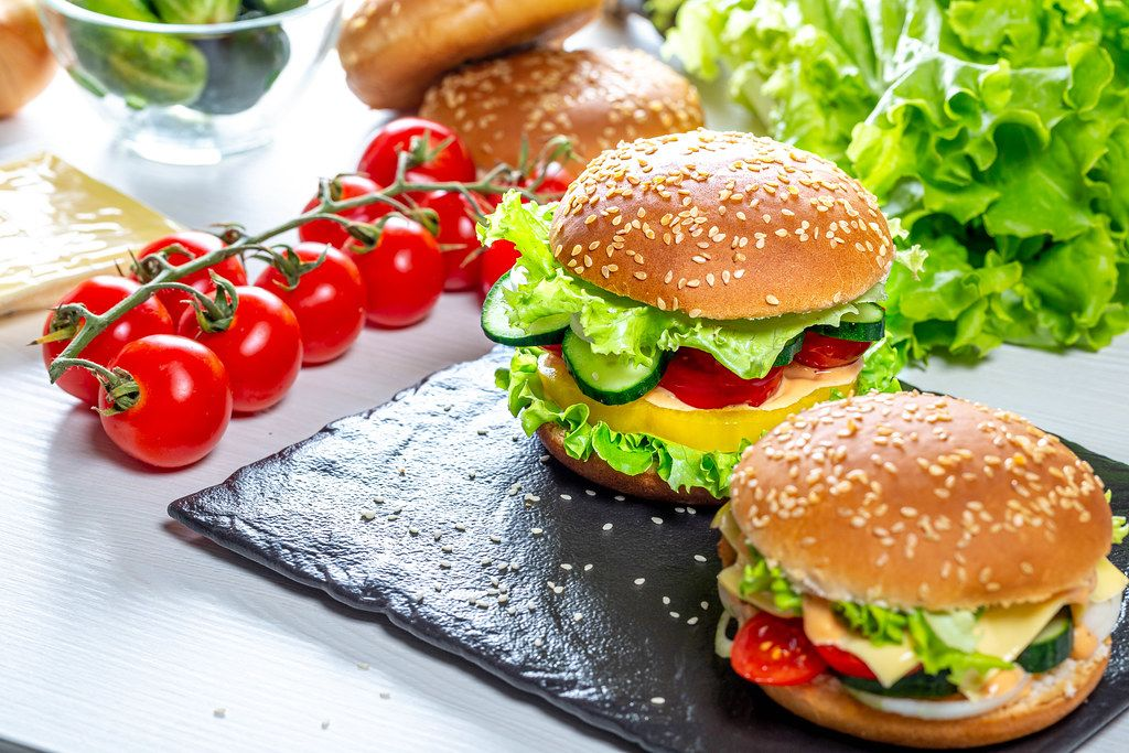 Two homemade hamburgers with fresh vegetables on black stone tray