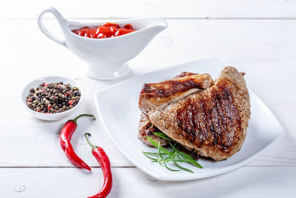 Two hot beef steaks on a white table with chili pepper and sauce