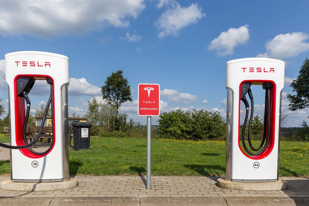 Two Tesla Supercharger Stations - electric vehicle charging network, in front of blue sky