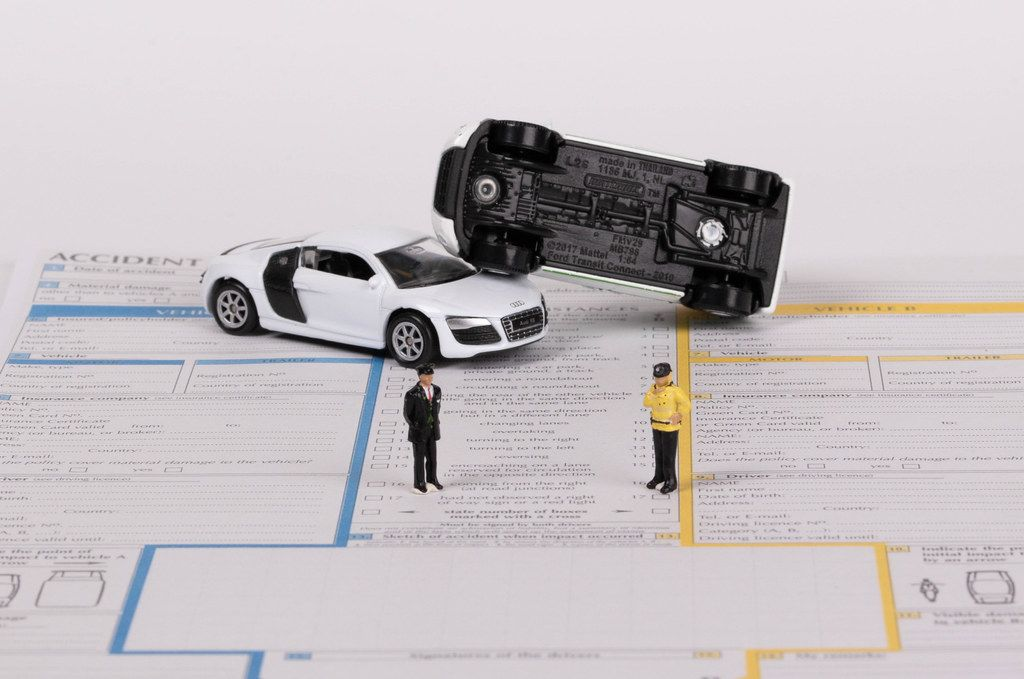 Two toy cars on accident statement report