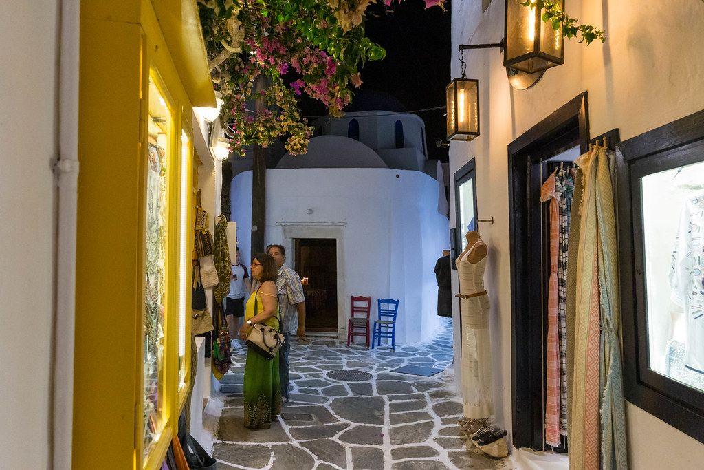 Typisch griechische, schmale Gasse mit Pflastersteinen und Verkaufsgeschäften in Naoussa auf Paros