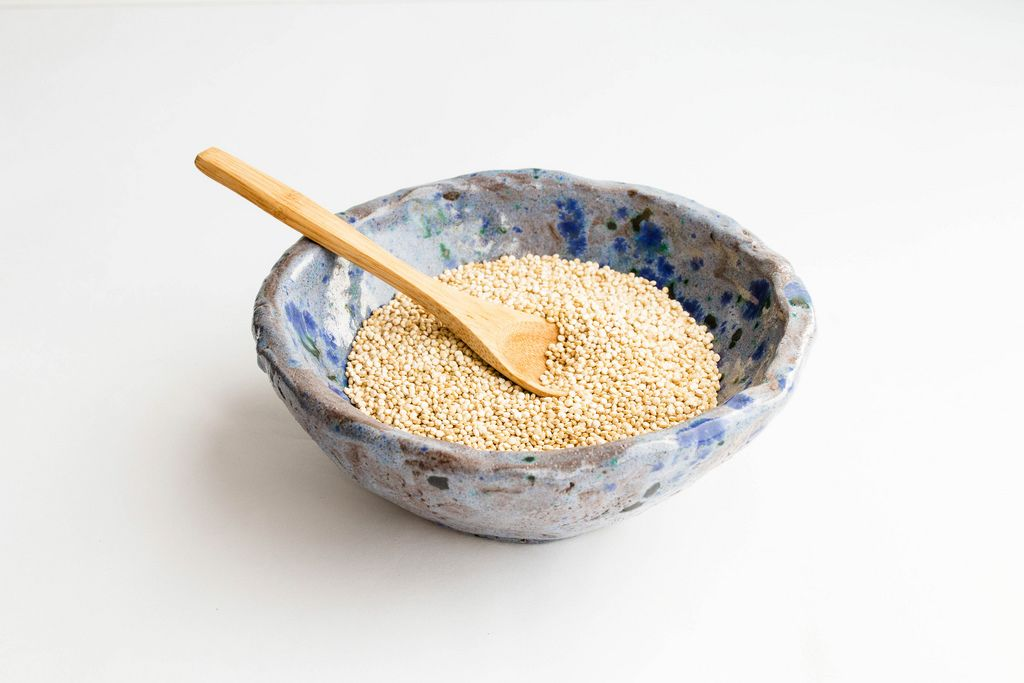 Uncooked white quinoa in a ceramic bowl on isolated on white background