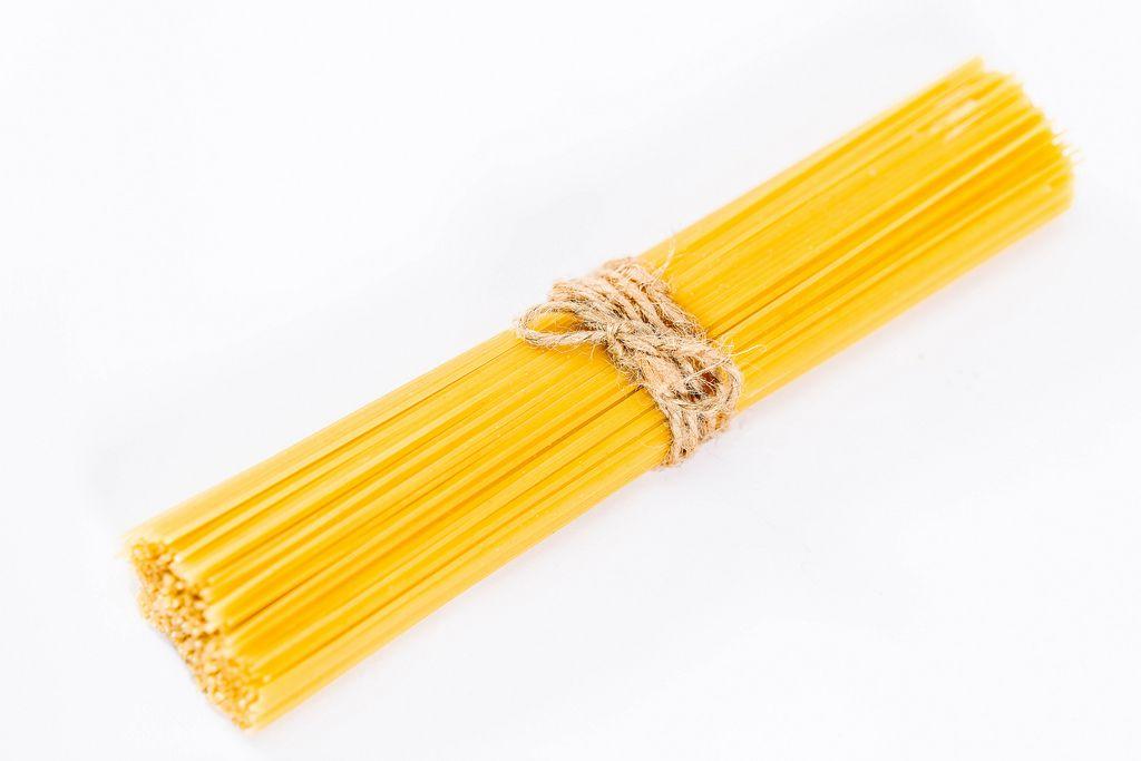Ungekochte Spaghetti mit Bastschnur gebunden vor weißem Hintergrund