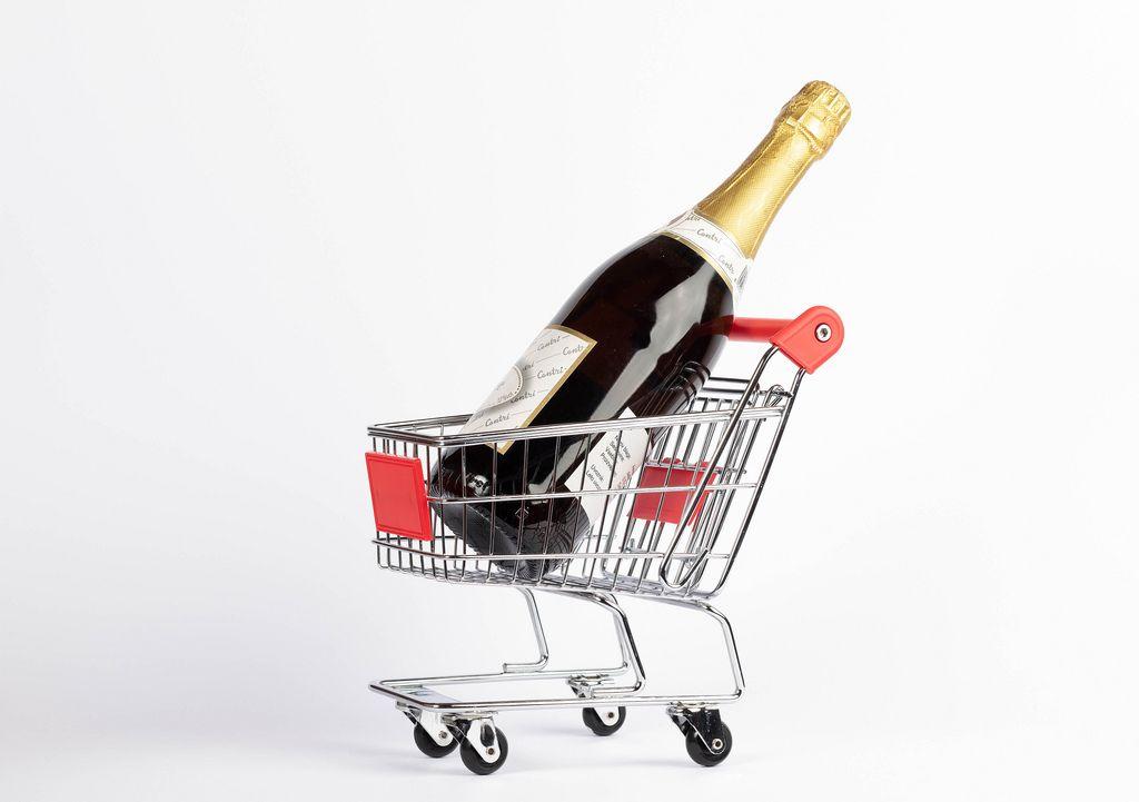 Ungeöffnete Champagnerflasche steht in kleinem Einkaufswagen vor weißem Hintergrund