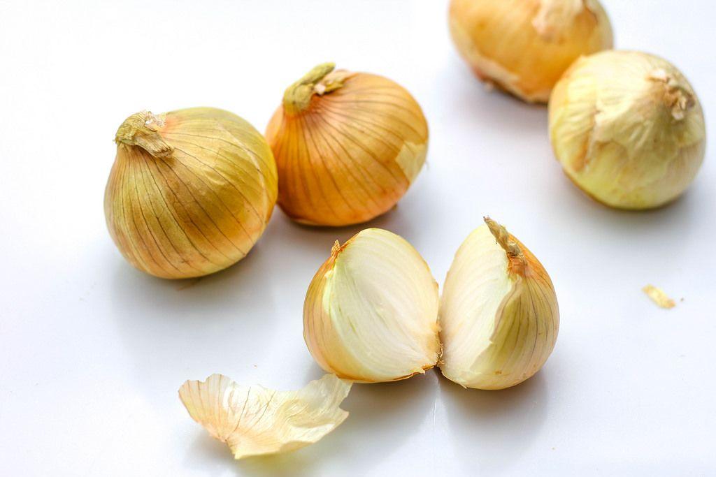 Ungeschälte Zwiebeln vor weißem Hintergrund