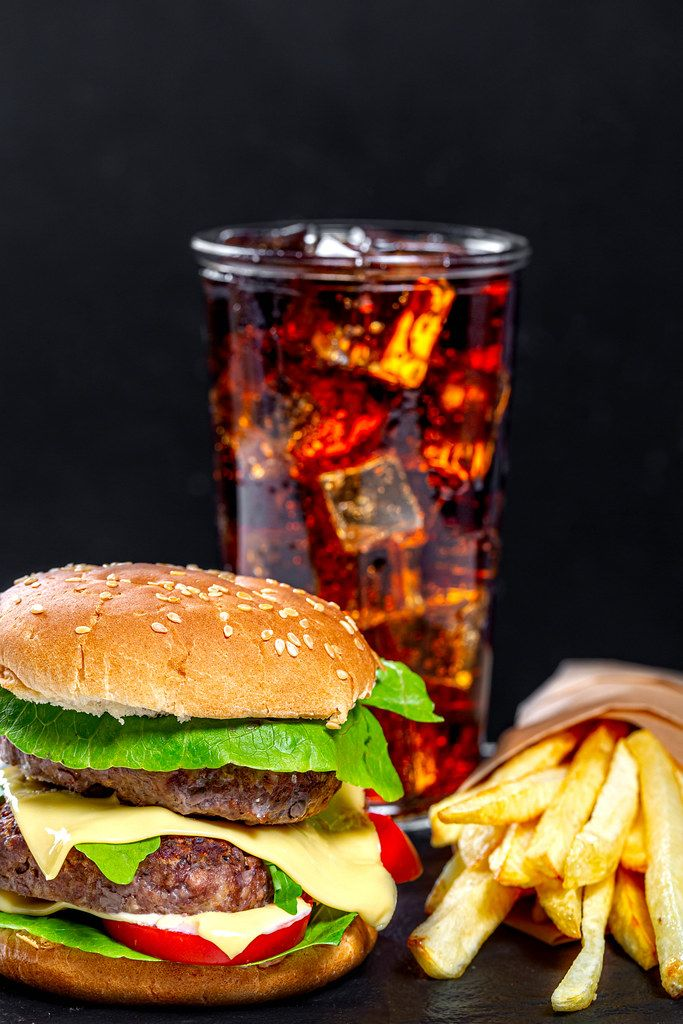 Unhealthy food concept-hamburger, Cola with ice cubes and fried artofel on black background