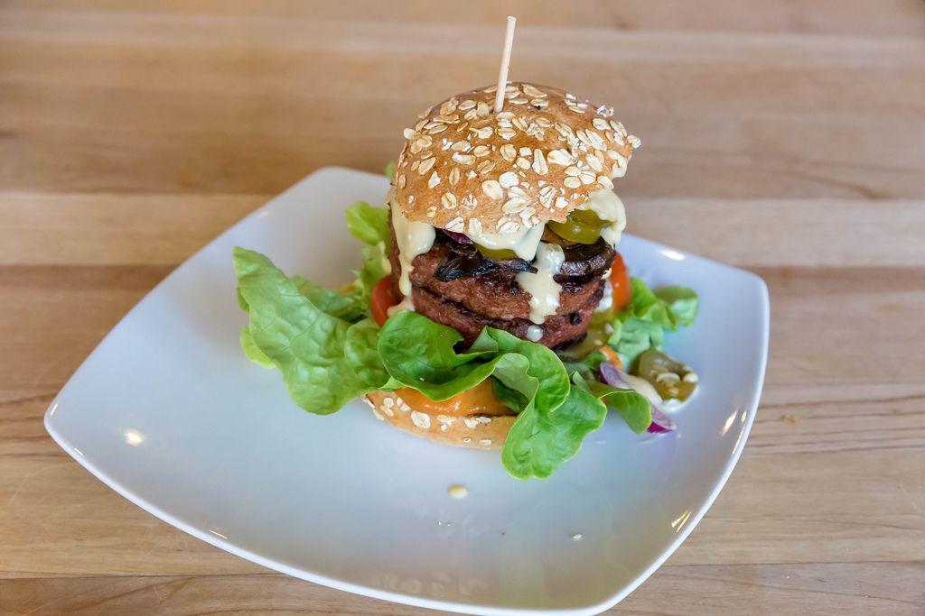 Unkonventionelles veganes Burger mit Beyond Meat Patty auf weißem Teller