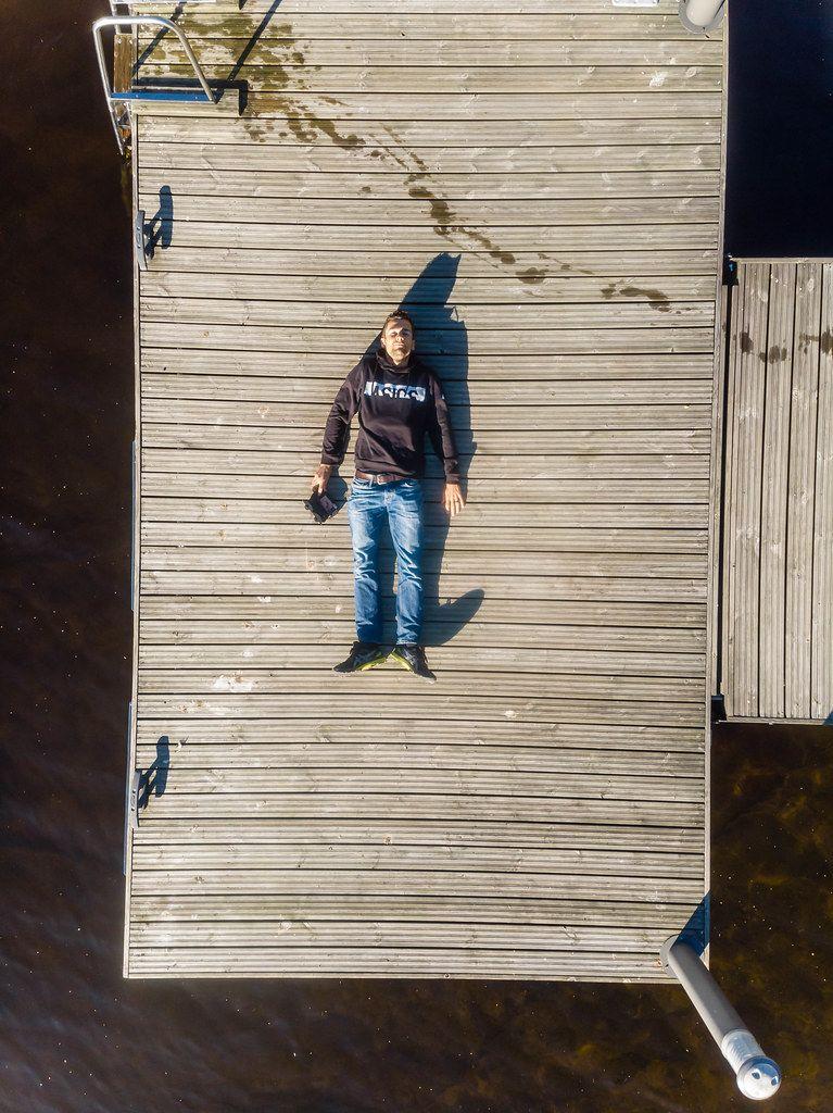 Urlauber macht ein Drohnen-Selfie, während er im Asics-Pulli auf einem Holzsteg unter der Sonne am nordischen Päijänne-See liegt