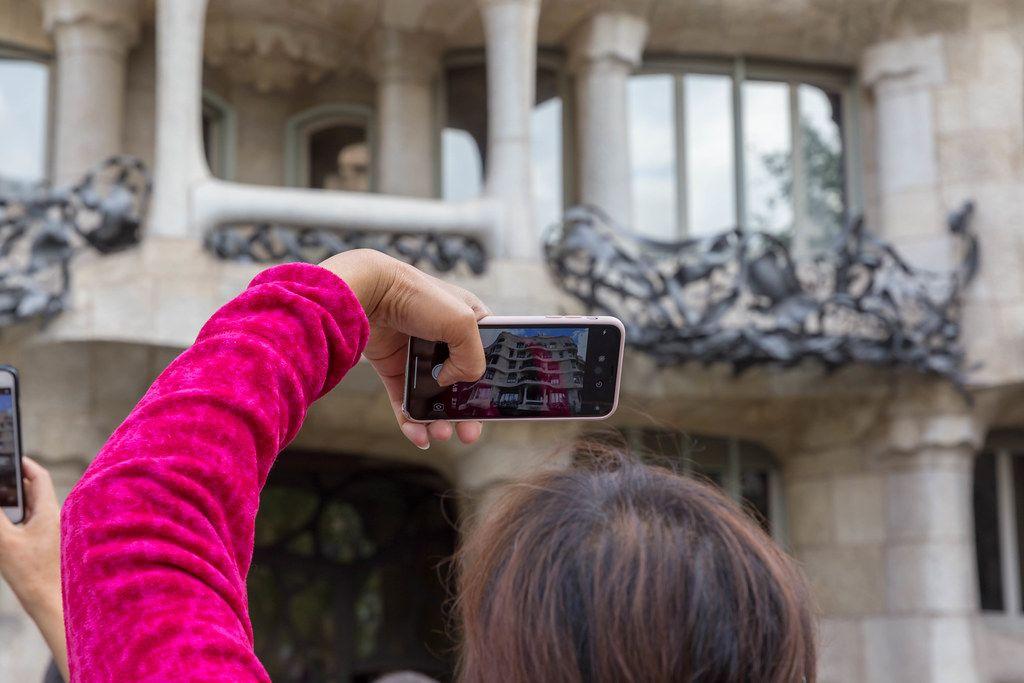 Urlauberin fotografiert mit ihrem Smartphone das Unesco Weltkulturerbe und Meisterwerk von Antoni Gaudi