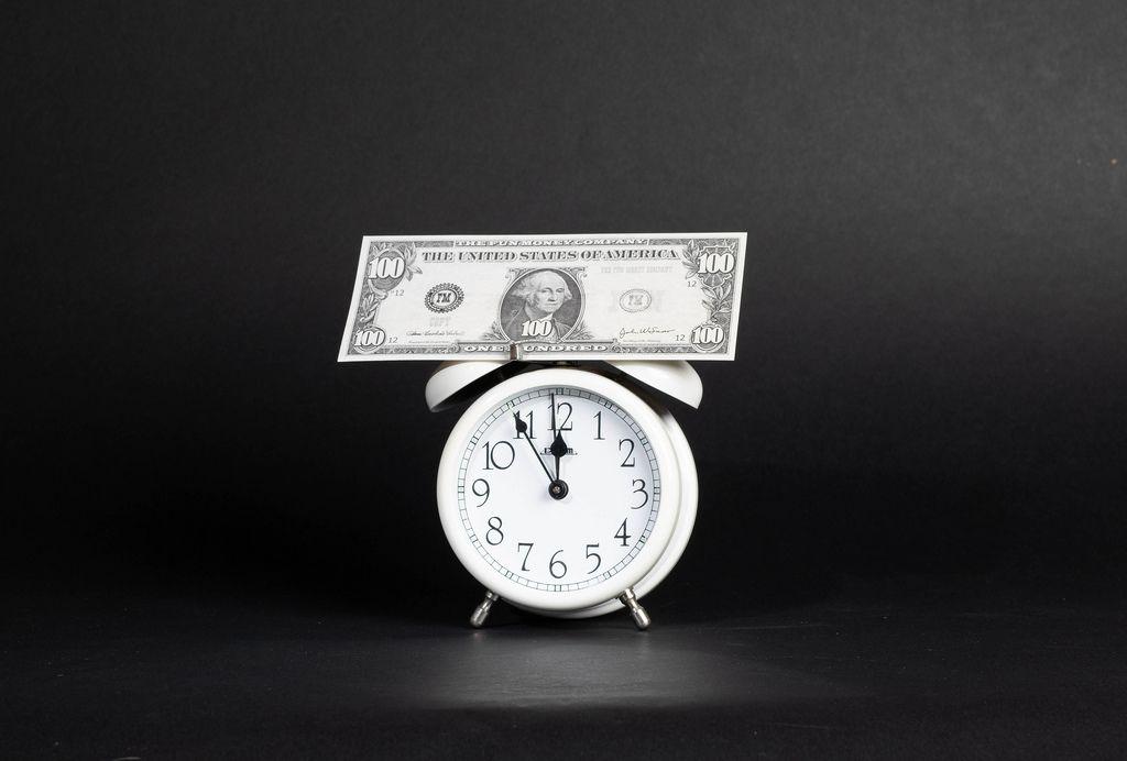 US-Dollar Banknote steht auf Wecker der auf 5 vor 12 steht vor dunklem Hintergrund