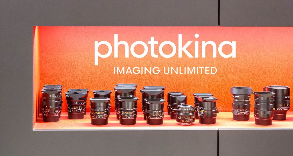 Various Leica lenses in front of an orange background, exhibited for the photo fair with the image title photokina imaging unlimited
