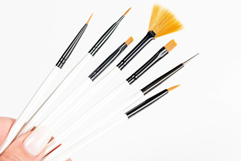 Various makeup brushes in a woman's hand on a white background