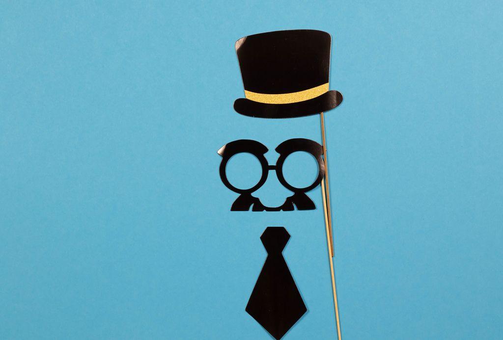 Vatertagsknozept - Papierhut, Brille mit Schnurrbart und Krawatte auf blauem Hintergrund