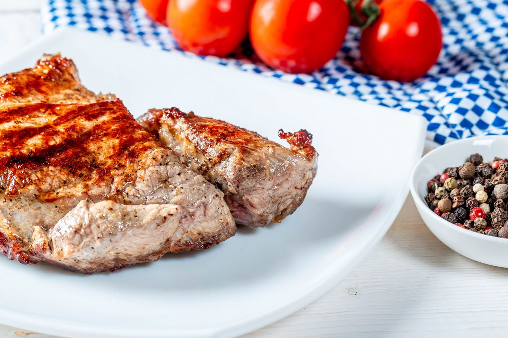 Veal steak on a white plate with spices and tomatoes