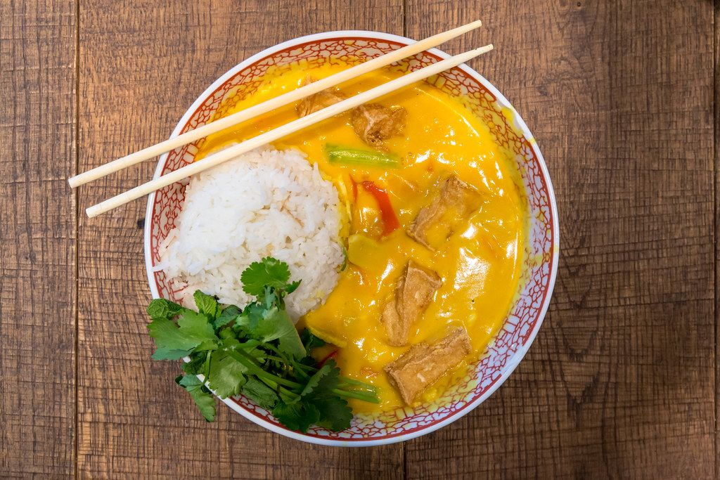 Vegan asian food at coa restaurant: yellow coconut curry with tofu, sweet pepper, mushrooms, sweet potatoes, rice, spinach, in a bowl with chopsticks