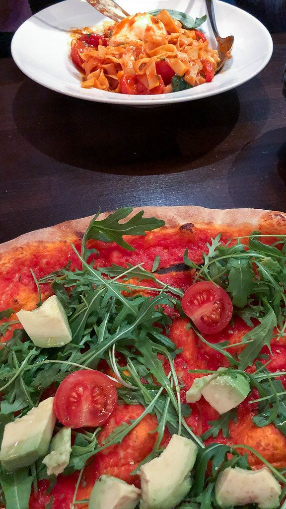 Vegan pizza (without cheese) with avocado, cherry tomatoes, rucola and tomato sauce. In the background, pasta with tomato sauce and cheese