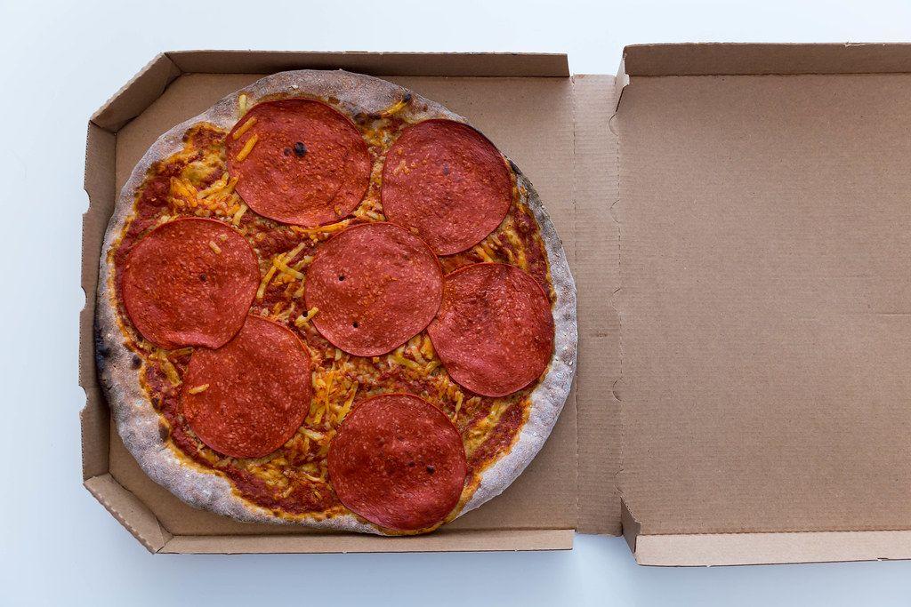 Vegane Pizza mit Salami von Vapiano im Karton zum Mitnehmen. Aufnahme von oben