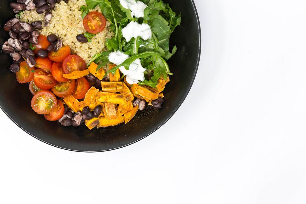 Veganes Essen in schwarzem Teller auf weißem Hintergrund Hello Fresh Kubanische Quinoa Bowl - mit Rucola mit Sauerrahm, schwarzen Bohnen, Kirschtomaten und zimtigen Süßkartoffeln