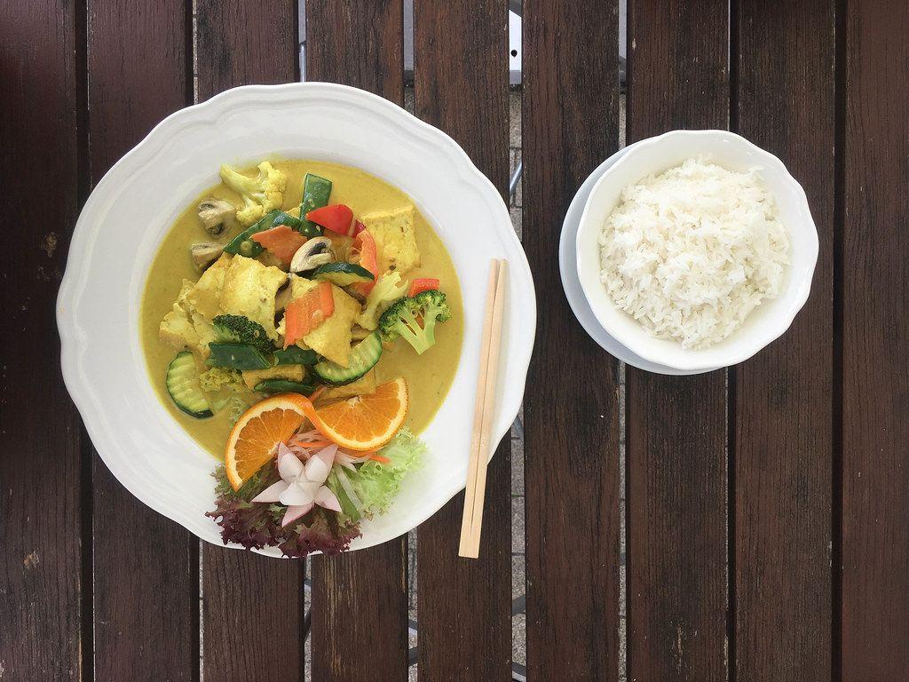 Veganes Essen mit Gemüse wie Brokkoli, Zucchini, Paprika und Blumenkohl, mit Tofu in fleischloser Curry-Kurkuma Soße, neben Essstäbchen und Reis