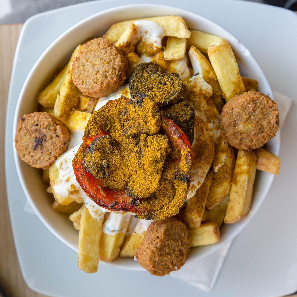 Veganes Gericht in Bunte Burger Köln: Pommes mit Falafel, orientalisches Gemüse, frischer Koriander, Aioli und Minz-Joghurt Sauce